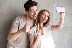 Image de l'homme joyeux et de la femme 20s de deux personnes prenant la photo de selfie image stock