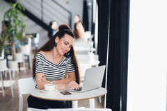 Image de la femme heureuse à l'aide de l'ordinateur portable tout en se reposant au café Jeune femme s'asseyant dans un café et p Images libres de droits