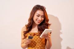 Image de la jeune dame enthousiaste d'isolement au-dessus du fond de biege utilisant le téléphone portable tenant la carte de cré photo stock