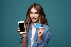 Image de la jeune dame enthousiaste d'isolement au-dessus du fond bleu utilisant le téléphone portable tenant le crédit photos libres de droits
