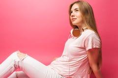 Image de la jeune femme assez gaie se tenant sur b rose photographie stock libre de droits