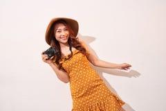 Image de la jeune femme de photographe d'isolement au-dessus de la caméra beige de participation de mur de fond photographie stock libre de droits