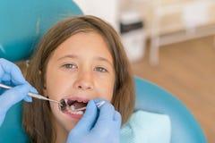 Image de la petite fille faisant vérifier ses dents par le docteur Petite fille au dentiste examinant une dent de perte avec un d photo libre de droits