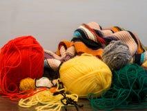 Image de laine, avec la couverture et les écheveaux tricotés colorés de la laine rouge, jaune et verte image libre de droits