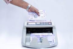 Image de main mettant la devise indienne comptant comptant la machine image stock