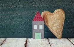 Image de maison de vintage et de coeur colorés en bois de tissu sur la table en bois devant le tableau noir Photos libres de droits