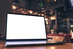 Image de maquette d'ordinateur portable avec l'écran blanc vide sur la table en bois Images stock