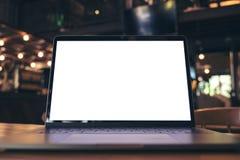Image de maquette d'ordinateur portable avec l'écran blanc vide sur la table en bois Photo stock