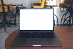 Image de maquette d'ordinateur portable avec l'écran de bureau blanc vide sur la table en bois Photo stock