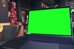 Image de maquette d'ordinateur portable avec l'écran vert vide sur la table en bois Images libres de droits