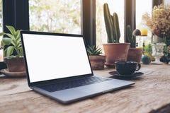 Image de maquette d'ordinateur portable avec la tasse de bureau blanche vide d'écran et de café sur la table en bois de vintage Photographie stock
