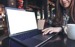 Image de maquette d'une femme à l'aide et présentant de l'ordinateur portable avec l'écran blanc vide sur la table en bois Photo libre de droits