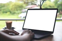 Image de maquette d'une femme à l'aide de l'ordinateur portable avec l'écran de bureau blanc vide avec la tasse de café Images stock