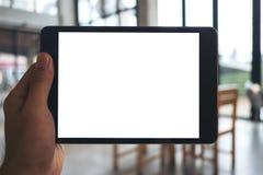 Image de maquette d'une main du ` s d'homme tenant et montrant le PC noir de comprimé avec l'écran blanc vide photographie stock