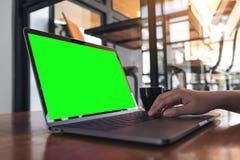 Image de maquette d'une main employant et dactylographiant sur l'ordinateur portable avec la tasse verte vide d'écran et de café  Photo libre de droits
