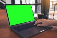 Image de maquette d'une main employant sur l'ordinateur portable avec la tasse verte vide d'écran et de café sur la table en bois Images stock