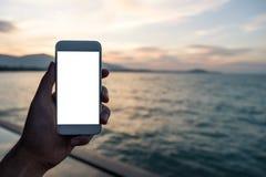 Image de maquette d'une main tenant et montrant le téléphone portable blanc avec l'écran de bureau vide devant la mer Photos stock