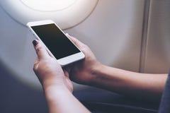 Image de maquette d'une main tenant et regardant le téléphone intelligent blanc avec l'écran de bureau vide à côté d'une fenêtre  Photographie stock