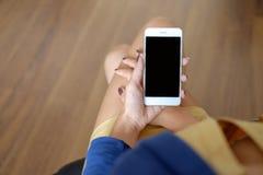 Image de maquette de la main du ` s de femme tenant le téléphone portable blanc avec l'écran noir sur la cuisse avec le fond en b photos stock