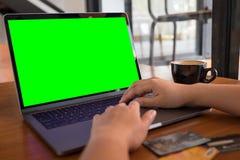 Image de maquette des mains dactylographiant sur le clavier d'ordinateur portable avec l'écran de bureau vert vide et les cartes  Photo stock