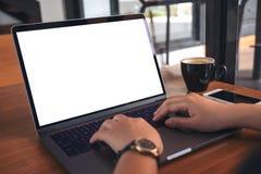 Image de maquette des mains employant et dactylographiant à l'ordinateur portable avec la tasse blanche vide d'écran, de téléphon Photographie stock libre de droits
