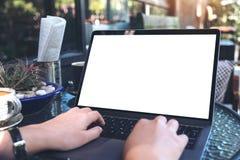 Image de maquette des mains employant et dactylographiant sur l'ordinateur portable avec la tasse blanche vide d'écran et de café Images libres de droits