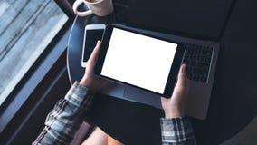 Image de maquette des mains tenant le PC noir de comprimé avec l'écran vide et l'ordinateur portable blancs, téléphone portable,  Photographie stock