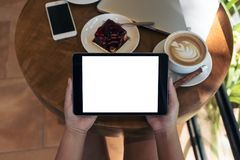 Image de maquette des mains tenant le téléphone portable blanc avec l'écran noir vide tout en mangeant le gâteau jaune de lait ca Image libre de droits