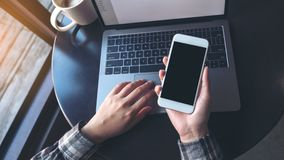 Image de maquette de femme d'affaires tenant le téléphone portable avec l'écran noir vide tout en à l'aide de l'ordinateur portab Photo stock