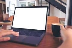 Image de maquette de l'utilisation d'une main et de l'ordinateur portable émouvant avec l'écran blanc vide tout en buvant du café Image libre de droits