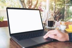 Image de maquette de l'utilisation d'une main et de l'ordinateur portable émouvant avec l'écran de bureau blanc vide sur la table Photo stock