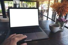 Image de maquette de l'utilisation d'une main et de l'ordinateur portable émouvant avec l'écran, la tasse de café et le vase à fl Image stock