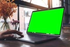 Image de maquette de l'utilisation d'une main et de l'ordinateur portable émouvant avec l'écran, la tasse de café et le vase à fl Photos libres de droits