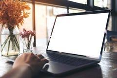 Image de maquette de l'utilisation d'une main et de l'ordinateur portable émouvant avec le vase de bureau blanc vide à écran et à Photo stock