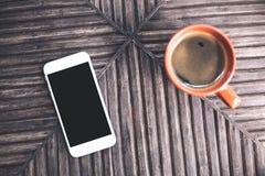 Image de maquette de vue supérieure d'un téléphone portable blanc avec l'écran de bureau noir vide et une tasse de café sur la ta Photographie stock