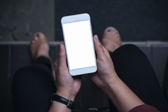 Image de maquette de vue supérieure d'une femme reposant et tenant le téléphone portable blanc avec l'écran vide avec le plancher photo libre de droits