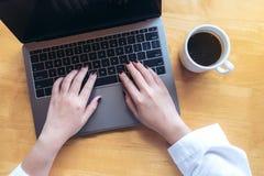 Image de maquette de vue supérieure des mains du ` s de femme employant et dactylographiant sur l'ordinateur portable avec la tas Images libres de droits