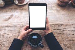 Image de maquette de vue supérieure des mains tenant le PC noir de comprimé avec la tasse blanche vide d'écran et de café sur la  Photo stock