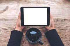 Image de maquette de vue supérieure des mains tenant le PC noir de comprimé avec la tasse blanche vide d'écran et de café sur la  Images stock
