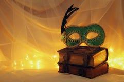 Image de masque vénitien élégant au-dessus de vieux livres de vintage devant le fond de Tulle Photos stock
