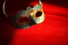 Image de masque vénitien élégant de bleu et d'or au-dessus de fond rouge Photographie stock