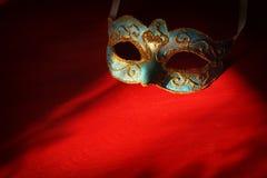 Image de masque vénitien élégant de bleu et d'or au-dessus de fond rouge Images stock