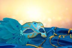 Image de masque vénitien élégant de bleu et d'or au-dessus de fond bleu de tissu en soie Image libre de droits