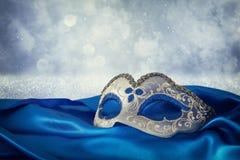 Image de masque vénitien élégant de bleu et d'or au-dessus de fond bleu de tissu en soie Images libres de droits