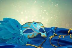 Image de masque vénitien élégant de bleu et d'or au-dessus de fond bleu de tissu en soie Photos stock