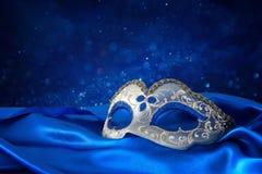 Image de masque vénitien élégant de bleu et d'or au-dessus de fond bleu de tissu en soie Images stock