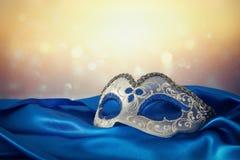 Image de masque vénitien élégant de bleu et d'or au-dessus de fond bleu de tissu en soie Photo stock