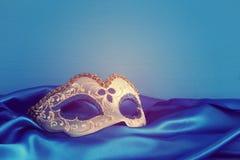 Image de masque vénitien élégant de bleu et d'or au-dessus de fond bleu de tissu en soie Image stock