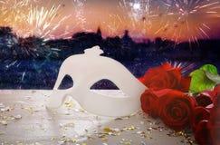 Image de masque vénitien élégant et de roses rouges au-dessus de table en bois devant le fond trouble de Venise Image stock