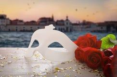 Image de masque vénitien élégant et de roses rouges au-dessus de table en bois devant le fond trouble de Venise Photos libres de droits